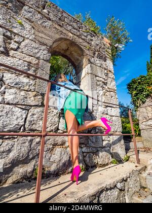 Pink high heels legs low view from rear rearview behind aft crop cropped lower waistdown body young woman looking through window opening of old house - Stock Photo