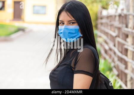 closeup to face of beautiful young latin woman with long black hair, wearing a mask, transparent blouse, outdoors