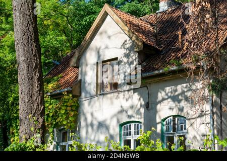 19th century house with tiled roof window. Front facade details, Beautiful old cottage in the forest.