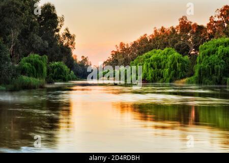 Lazy plains Macquarie river flowing through Dubbo city in Australian Great Western Plains at sunrise.