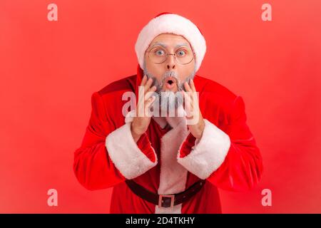 Portrait of extremely surprised man in red santa claus costume looking at camera with shocked wondered expression, can't believe in coming holidays an