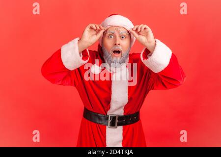 Portrait of extremely shocked surprised santa claus looking at camera with big wondered eyes holding eyeglasses on forehead, holidays coming. Indoor s