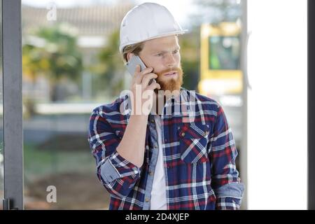 smiling architect with safety helme having a phone call - Stock Photo