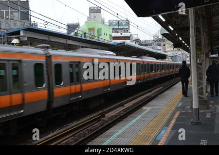 Tokyo, Japan-02/23/16: People walking along the train platform as the local train travels down the rail line at a great speed.