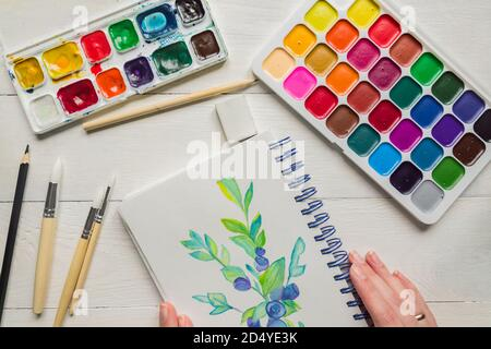 Female hand sketching aquarelle painting of blueberry branch. Watercolor paints and brushes, top view. Creative artistic flat lay