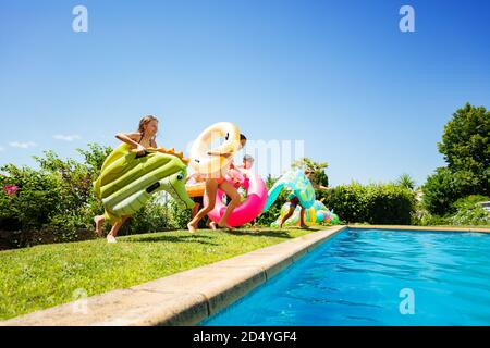 Group of many young kids run and jump into the swimming pool holding inflatable buoy toys diving in the water - Stock Photo