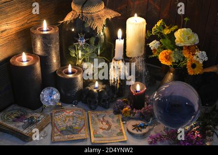 Mysterious still life with old tarot cards, crystal ball and black candles on witch table. Esoteric, gothic and occult background with magic objects.