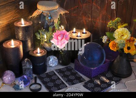Mysterious still life with tarot cards, black candles and crystal ball on witch table. Esoteric, gothic and occult background with magic objects. Hall