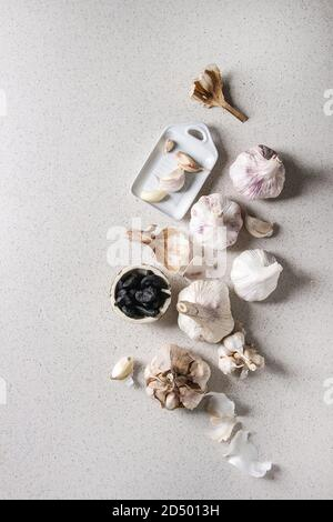 Variety of fresh organic garlic bulbs whole and peeled and cloves of black fermented garlic with ceramic grater over grey spotted background. Flat lay