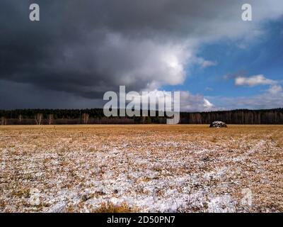 A view of a dry grass field with first snow and a dark cloudy sky. Early winter or late autumn. Scenery - Stock Photo
