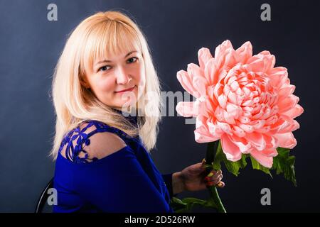 Woman demonstrates a huge pink flower hand made of paper.