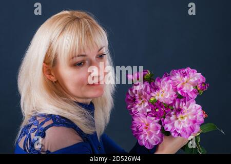 Portrait of a blonde woman with dahlia flowers