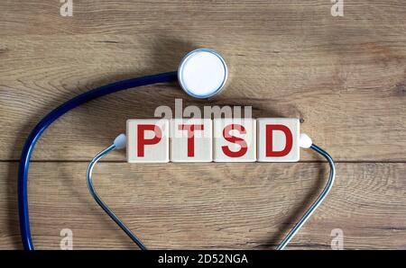 Concept word 'PTSD, post-traumatic stress disorder' on cubes on a beautiful wooden background. Stethoscope. Copy space, medical concept.