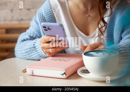 Young woman in blue warm sweater is reading a text message from mobile phone while drinking coffee