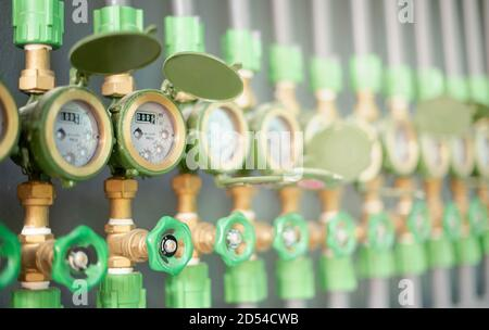 Row of industrial pipelines and valves with green wheels on  grey wall for check the standard water level located at the dormitory for check the price - Stock Photo
