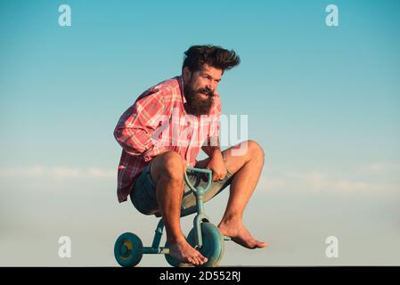 Portrait of a bearded man bicyclist, crazy hipster having fun with bicycle outdoors. Stock Photo