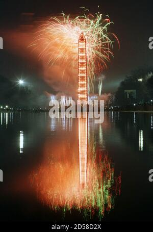 The Washington Monument lights up and is reflected in the reflecting pool during the millennium celebration in Washington January 1. Washington ushered in 2000 with rap, rock, a Steven Spielberg film, fireworks by the Washington Monument and - for a hardy few - a midnight wade in the reflecting pool in front of the Lincoln Memorial.  MMR/SV - Stock Photo