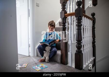 Six year old boy reading a book whilst sat on his residential home staircase, England, United Kingdom