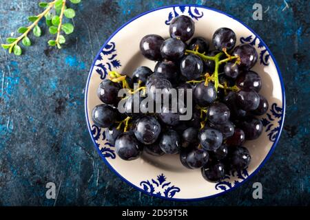 Fresh black grapes and leaves in dish on dark background.