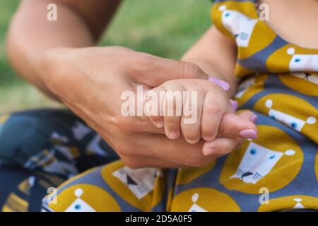 A baby hand holds mothers hand. Happy family and baby protection concept Stock Photo