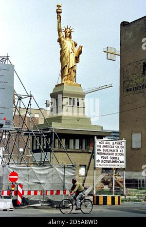 A cyclist passes a giant copy of the 'Statue of Liberty ', May 29 which has been set up on top of a former east-German border guard watchtower at the former allied Checkpoint Charlie which is now a large construction site where U.S. investors build the American trade center. The sign reads in English, Russian, French and German ' You are leaving the American sector