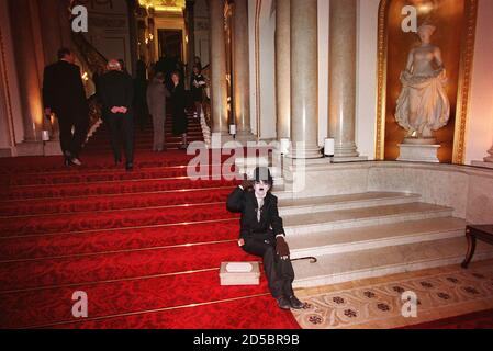 An entertainer sits on the steps inside Buckingham Palace November 13. The Queen hosted a party at the Palace for Prince Charles' 50th birthday.  AS/SB - Stock Photo