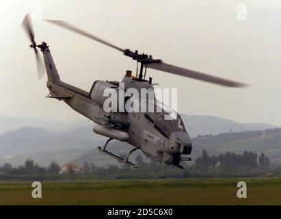 A U.S. Marines AH-1W Super Cobra gunship flies low over Albania May 9. The Aviation Combat Element (ACE) for the 26th Marine Expeditionary Unit (MEU) includes 12 CH-46E Sea Knight transport chopers, four CH-53E Super Stallion heavy-lift chopers, four AH-1W Super Cobra gunships, two UH-1N utility chopers and six AV-8B Harrier attack jets. **DIGITAL IMAGE** - Stock Photo
