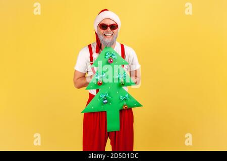 Extremely happy elderly man in santa claus costume and stylish sunglasses holding paper christmas tree looking at camera with toothy smile. Indoor stu
