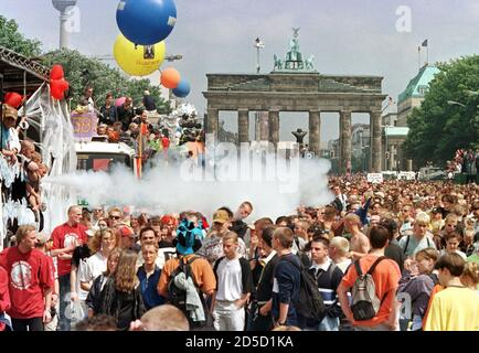 Revellers at Berlin's famous landmark, the Brandenburg Gate, watch floats make their way through the dense masses during the German capital's annual 'Love Parade' techno music fest July 11. Over a million people are expected to attend this year's tenth anniversary street parade with the motto 'One World, One Future'. - Stock Photo