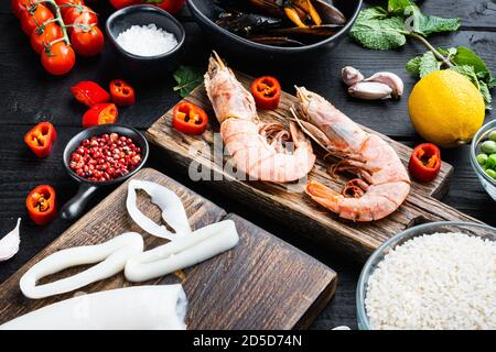 Uncooked spanish paella ingredients with king prawns, cuttlefish, mussels and herbs on black wooden table Stock Photo
