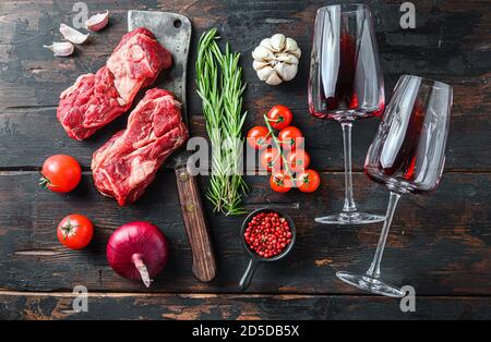 Organic raw chuck eye roll beef steak over old butcher cleaver near red wine glasses with herbs and seasonings on old dark wooden table. Top view.