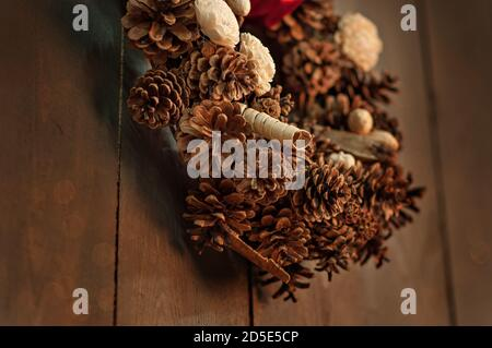 On a wooden brown wall background with blurred bokeh in a dark loft hangs a wreath made by hands of pine cones, dried flowers, decorative elements, - Stock Photo