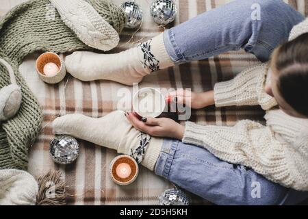 Young woman sits on plaid in cozy knitted woolen white sweater and socks holds cup of cocoa in her hands. Hygge New Year, cozy Christmas, preparation