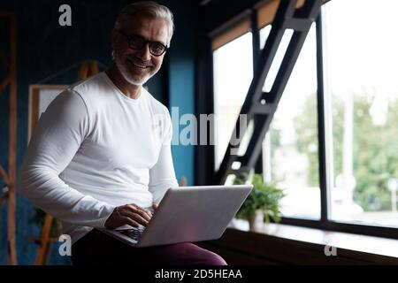 Casual Grey-haired Mature Male business executive using laptop in office. - Stock Photo