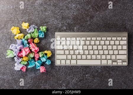 Top view flat lay of many crumpled paper stick note ball with computer keyboard on office desk concrete background no idea concept with copy space for - Stock Photo