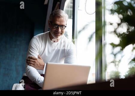 Casual Grey-haired Mature man in eyeglasses working on laptop while sitting in office or cafe near the window