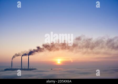 Horizontal snapshot of three smoking stacks of thermal power station on the horizon taken from the hill, pipes are in evening fog on blue sky, copy space