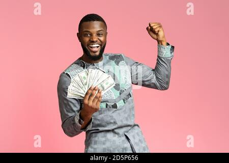 Happy african american man holding cash on pink