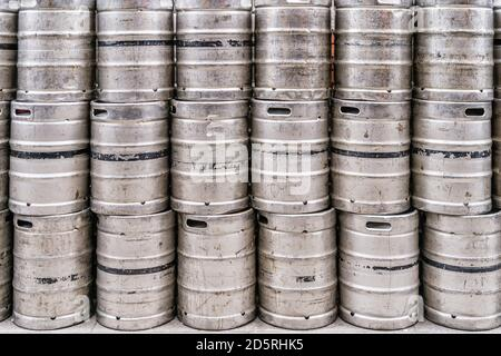 Wall of used and scratched stainless steel beer barrels or kegs. Stacked in a row large silver or metallic colour alcohol barrels or containers - Stock Photo