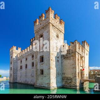 Scaligero Castle Castello di Sirmione fortress from Scaliger era in historical center of Sirmione town on Garda lake, medieval castle with stone towers, brick walls and water moat, Lombardy, Italy