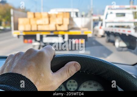 driver hand on the steering wheel of a car, in front of a truck with a dangerous cargo of lumber
