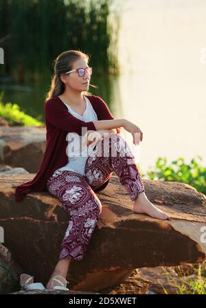 A woman sat on the rock at lakeside