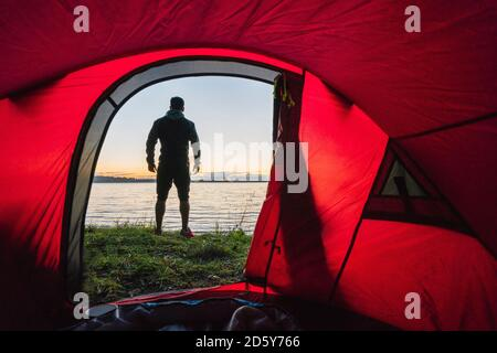 Man camping in Estonia, standing in front of tent, watching sunset