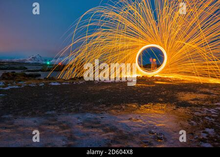 Norway, Lofoten, Ballstad, Spinning burning steel whool on the harbor - Stock Photo