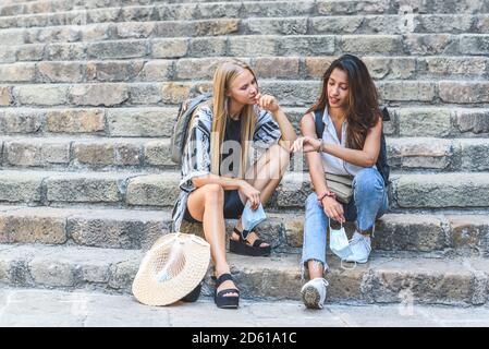 young attractive indian woman looking to watch and sharing the timing with blonde caucasian friend. both sitting on ancient stone stairs