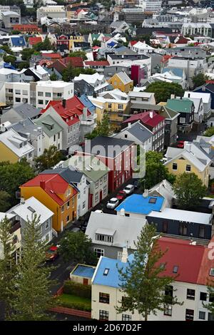 A view from the top of Hallgrimskirkja Church tower. Rows of brightly coloured, modern Scandinavian houses can be seen across Reykjavik city, Iceland.