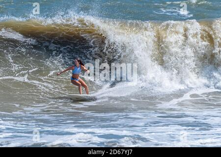 Female surfer enjoying a big wave day at The Poles in Jacksonville, Florida. (USA) - Stock Photo