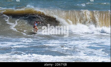 The combination of a Nor'easter and Hurricane Teddy swells produced overhead waves for adventurous surfers at The Poles in Jacksonville, Florida. - Stock Photo