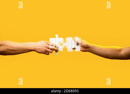 Man hands connecting couple puzzle piece. Business solutions, target, success, goals and strategy concepts. Hand connecting jigsaw puzzle. Business