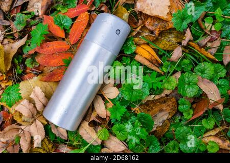 A can of deodorant or air freshener thrown out on the lawn in the autumn grass